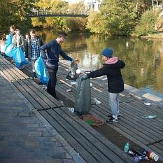 Das Foto zeigt Studierende, die mit Papierzangen und Abfallsäcken die Lahnterrassen von Müll befreien.©Universitätsstadt Marburg, Ute Schneidewindt