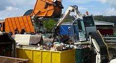 Das Foto zeigt ein Pressmüllfahrzeug beim Abladen auf dem Servicehof. Das Material wird direkt mit einem Bagger vor Ort verdichtet.