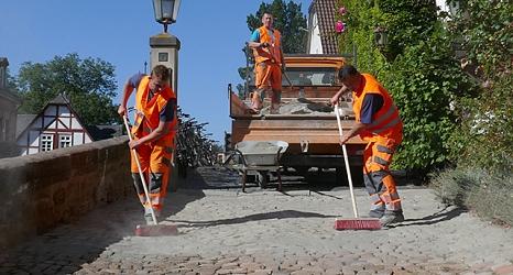 Das Foto zeigt drei Mitarbeiter des DBM mit einem Pritschenfahrzeug im Hintergrund beim Absanden.©DBM, Sonja Stender
