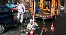 Das Bild zeigt einen Mitarbeiter des DBM, der bereits bis zur Körpermitte in einen Schacht hinabgestiegen ist. Er ist durch ein Seil gesichert und trägt einen Ganzkörperanzug.