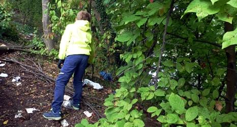 Das Foto zeigt einen Jungen, der mit einer Papierzange den Müll eines Picknicks am Lahnufer einsammelt.©DBM, Sonja Stender