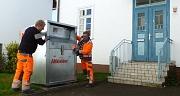 Mitarbeiter des DBM stellen einen Altkleidercontainer neben den Eingang des Ginseldorfer Bürgerhauses.