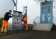 Mitarbeiter des DBM stellen in Ginseldorf einen Altkleidercontainer neben den Eingang des Bürgerhauses.