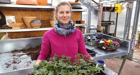 Das Foto zeigt eine Auszubildende in der Stadtgärtnerei mit einer Palette frisch getopfter Pflanzen.©DBM, Sonja Stender