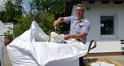 Das Foto zeigt Betriebsleiter Ralf Schmidt beim Befüllen eines Sandsacks.