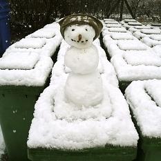 Das Bild zeigt eingeschneite Biotonnen, von denen eine mit einem kleinen Schneemann verziert ist.©DBM, Sonja Stender