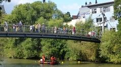 Das Foto zeigt das Boot der DLRG mit Besatzung unter der Luisa-Heuser-Brücke auf dem Weg zu den Bojen. Passanten beobachten die Aktion von der Brücke aus.