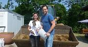 Das Foto zeigt Julia Nestle und Daniel Fischer mit Schaufel und Sandsack vor einer Radladerschaufel auf dem Servicehof Am Krekel.
