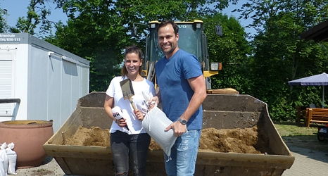 Das Foto zeigt Julia Nestle und Daniel Fischer mit Schaufel und Sandsack vor einer Radladerschaufel auf dem Servicehof Am Krekel.©DBM, Sonja Stender