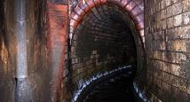 Das Bild zeigt ein gemauertes Eiprofil mit einer Höhe von 1,70 m. Bei sehr starken Regen können selbst solche großen Leitungen komplett mit Wasser gefüllt sein. Im Vordergrund kann man die Sandstein-Rutsche erkennen, mit deren Hilfe das Wasser vom Parkhau