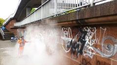 In einer Wolke aus Wasserdampf verschwindet nicht nur der Mitarbeiter des DBM, sondern auch die Graffiti.
