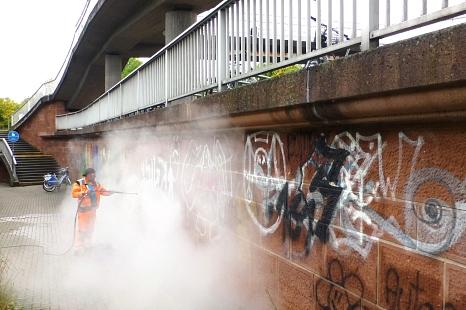 In einer Wolke aus Wasserdampf verschwindet nicht nur der Mitarbeiter des DBM, sondern auch die Graffiti.©Sonja Stender, Dienstleistungsbetrieb der Stadt Marburg
