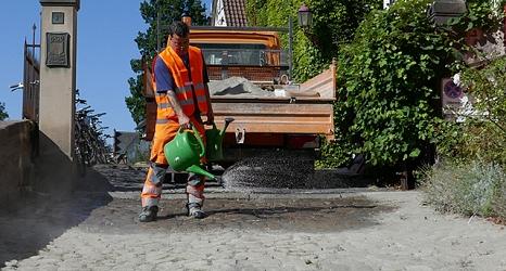 Das Foto zeigt einen Mitarbeiter des DBM beim Gießen der abgesandeten Fläche.©DBM, Sonja Stender