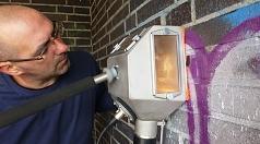 Mit enormer Kraft und gut abgeschirmt unter der Saugglocke setzen die kleinen, auftreffenden Körnchen dem Graffito mächtig zu. Patrick Klein zielt mit der Düse auf die farbverschmierten Wände. So sollen illegale Graffiti und inhaltsleere Farbschmierereien
