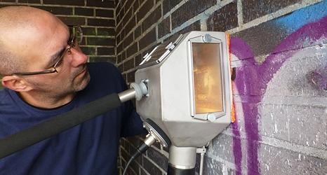 Mit enormer Kraft und gut abgeschirmt unter der Saugglocke setzen die kleinen, auftreffenden Körnchen dem Graffito mächtig zu. Patrick Klein zielt mit der Düse auf die farbverschmierten Wände. So sollen illegale Graffiti und inhaltsleere Farbschmierereien©DBM, Sonja Stender
