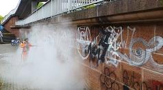 Das Foto zeigt einen Mitarbeiter des DBM bei der Beseitigung von Graffiti mit einem Dampfstrahler.