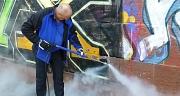 Das Foto zeigt einen Mann beim Beseitigen eines Graffitos auf einer Sandsteinmauer mit einem Hochdruckreiniger.