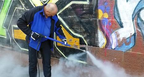 Das Foto zeigt einen Mann beim Beseitigen eines Graffitos auf einer Sandsteinmauer mit einem Hochdruckreiniger.©DBM, Sonja Stender