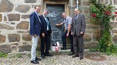 Das Foto zeigt Fachbereichsleiter Walter Ruth, Bürgermeister Wieland Stötzel und vom DBM Abteilungsleiter Straßenreinigung Ralf Schmidt sowie Betrieblseiter Joachim Brunnet vor der halb gereinigten Tür des Rathausgebäudes.