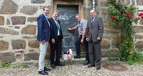 Das Foto zeigt Fachbereichsleiter Walter Ruth, Bürgermeister Wieland Stötzel und vom DBM Abteilungsleiter Straßenreinigung Ralf Schmidt sowie Betrieblseiter Joachim Brunnet vor der halb gereinigten Tür des Rathausgebäudes.©DBM, Sonja Stender
