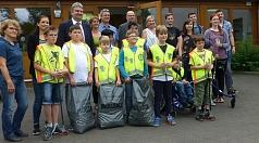 Das Foto zeigt die Kinder der Mosaikschule mit Warnwesten, Müllsäcken und Papierzangen. In der hinteren Reihe stehen die verantwortlichen Lehrerinnen der Mosaikschule und Mitarbeiter/innen des DBM mit dem Bürgermeister Wieland Stötzel.