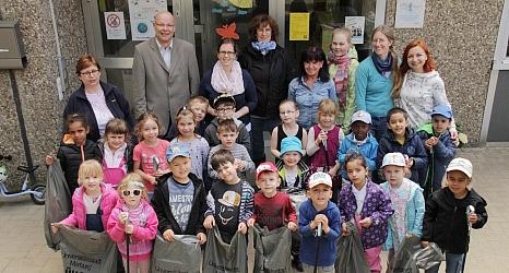 Das Foto zeigt DBM-Betriebsleiter Joachim Brunnet mit den Kindern und Erzieherinnen der Kindertagesstätte Graf-von-Stauffenberg-Straße 1 a, die ihre gefüllten Müllsäcke präsentieren.©Universitätsstadt Marburg