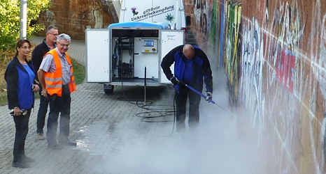 Das Foto zeigt den Mann mit dem Hochdruckreiniger und Führungskräfte des DBM bei der Begutachtung der Arbeitsergebnisse.©DBM, Sonja Stender