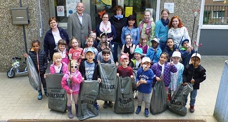 Das Foto zeigt die Kinder der KiTa Graf-von-Stauffenberg-Straße mit Papierzangen und Säcken nach dem Abfallsammeln mit ihren Erzieherinnen und dem Betriebsleiter des DBM, Joachim Brunnet.©DBM, Sonja Stender