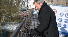 Oberbürgermeister Dr. Spieß entfernt ein Liebesschloss vom Geländer der Weidenhäuser Brücke.
