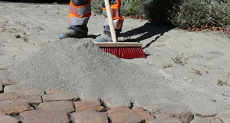 Das Foto zeigt einen kleinen Berg Sand bevor er mit einem Straßenbesen in die Ritzen im Kopfsteinpflaster gefegt wird.©DBM, Sonja Stender