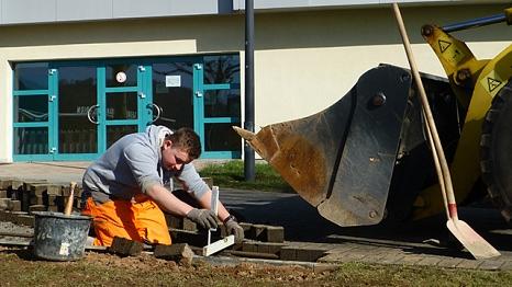 Das Foto zeigt einen Auszubildenden des DBM beim Pflastern eines Weges.©DBM, Sonja Stender