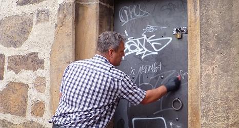 Das Foto zeigt Ralf Schmidt, den Abteilungsleiter der Straßenreinigung beim Entfernen von Graffiti an einer Tür auf der Rückseite des Rathausgebäudes.©DBM, Sonja Stender
