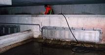 Das Foto zeigt einen Mitarbeiter des DBM beim Reinigen des Vorbeckens eines großen Regenrückhaltebeckens.