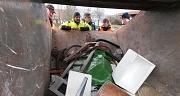 Das Foto zeigt Aktive des Sauberhaften Frühjahrsputz in Elnhausen wie sie in die gefüllte Abfallmulde schauen.