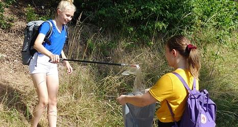 Das Foto zeigt zwei Mädchen der Steinmühle, die mit einer Papierzange den Abfall in einen Müllsack befördern.©privat