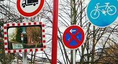 Das Foto zeigt verschiedene Schilder und einen Verkehrsspiegel an einem Mast.