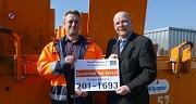 Das Foto zeigt Servicehofleiter Ralf Schmidt und Betriebsleiter Joachim Brunnet mit einem Schild, auf dem die neue Telefonnummer des Servicehofs steht.
