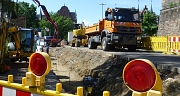 Das Foto zeigt Kräne, Bagger und LKW auf der Baustelle am rudolphsplatz.